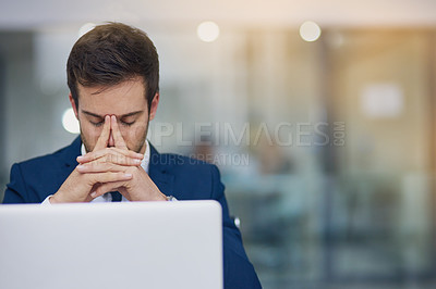 Buy stock photo Shot of a young businessman looking stressed while working in his office