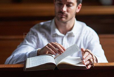 Buy stock photo Shot of a young man reading the bible in church