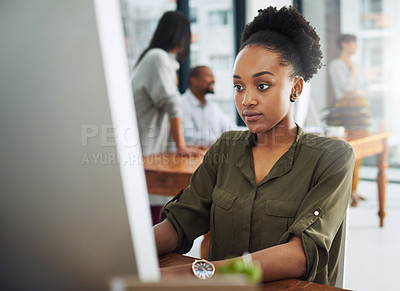 Buy stock photo Cropped shot of a young businesswoman working on a computer in a modern office with colleagues in the background