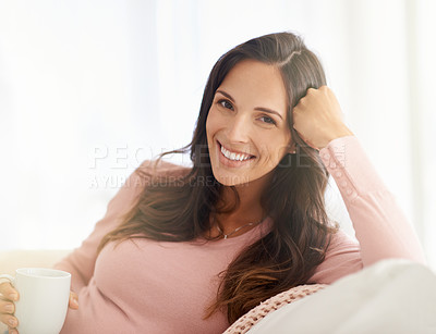 Buy stock photo Shot of a young woman having a warm beverage and relaxing at home