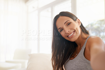 Buy stock photo Shot of a young woman taking a selfie at home