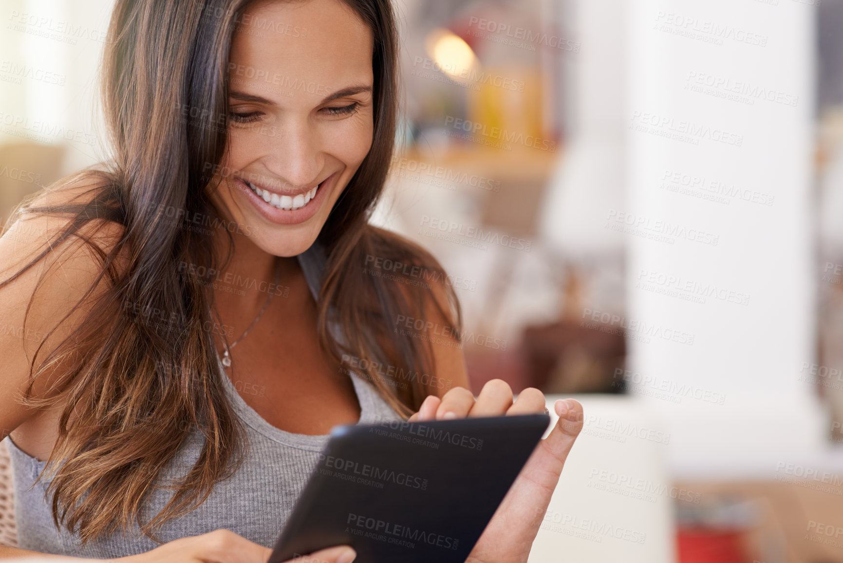 Buy stock photo Cropped shot of a woman using her tablet while relaxing at home