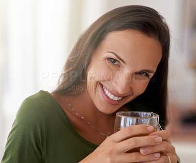 Buy stock photo Shot of a young woman relaxing at home with a glass of tea