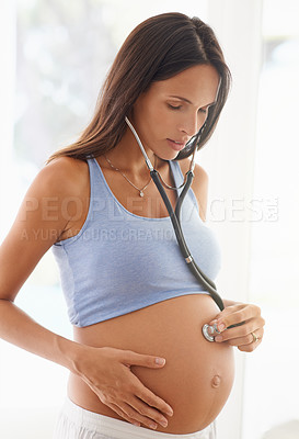 Buy stock photo Shot of a pregnant woman using a stethoscope to listen to her baby's heartbeat