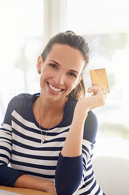 Buy stock photo Portrait of a young woman using a credit card to make an online payment at home