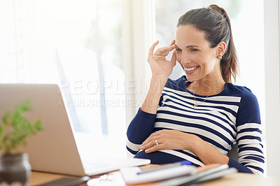 Buy stock photo Cropped shot of a young pregnant woman working on a laptop at home