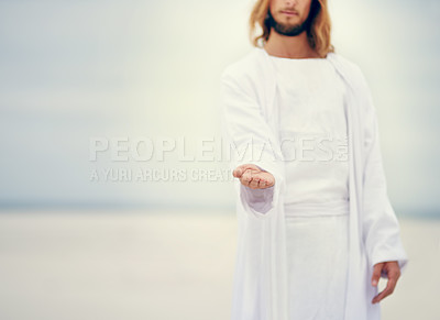 Buy stock photo Shot of Jesus standing with his hand outstretched on a bare landscape