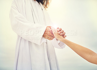 Buy stock photo Shot of Jesus standing with his hand outstretched toward a follower on a bare landscape