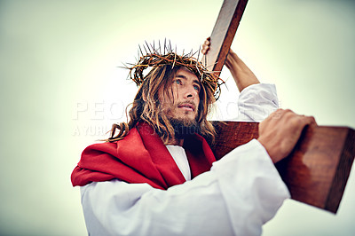Buy stock photo Shot of Jesus carrying his cross across a bare landscape
