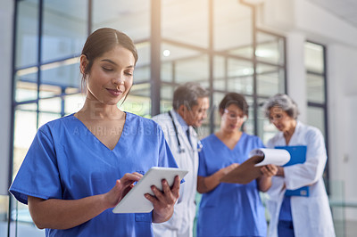 Buy stock photo Cropped shot of a medical practitioner looking at a patient's file on a digital tablet with colleagues in the background