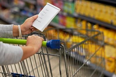 Buy stock photo Closeup shot of a woman checking her shopping list in a grocery store
