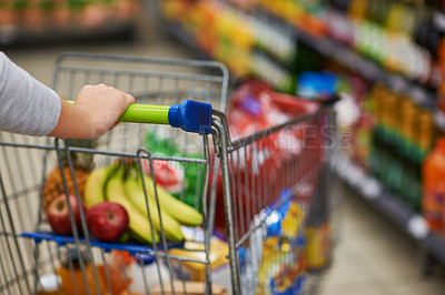 Buy stock photo Closeup shot of a woman pushing her trolley full of groceries in a supermarket