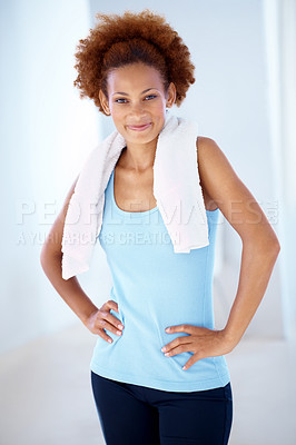 Buy stock photo Portrait of a fitness young woman with towel around her neck posing in the gym