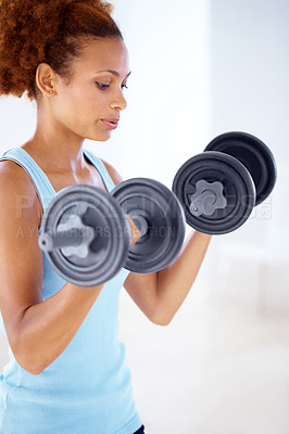 Buy stock photo African american young woman exercising with heavy weight dumbbells looking focused - copyspace