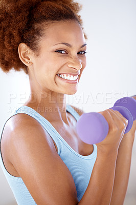Buy stock photo Portrait of a healthy young woman working out with dumbbells and smiling at you