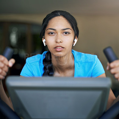 Buy stock photo Portrait of a fit young woman using wireless earphones while working out on a treadmill