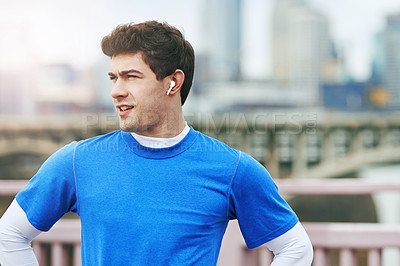 Buy stock photo Shot of a fit young man using  wireless earphones while out for a run in the city