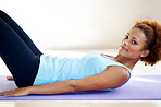 Young fitness woman lying on a yoga mat