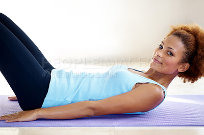 Buy stock photo Portrait of an attactive young woman lying on a yoga mat and exercising