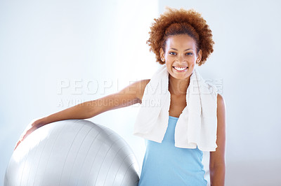 Buy stock photo Portrait of young female fitness instructor holding a pilates ball and smiling