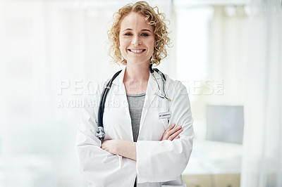 Buy stock photo Portrait of a smiling female doctor standing in a hospital corridor with her arms crossed