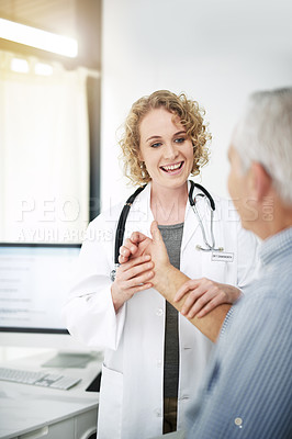 Buy stock photo Shot of a doctor examining a senior patient's wrist in her office