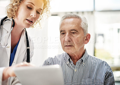 Buy stock photo Shot of a doctor showing a senior patient some information on a digital tablet in her office