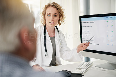 Buy stock photo Shot of a doctor explaining a treatment on a monitor to a senior patient in her office