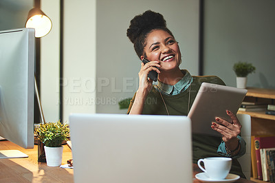 Buy stock photo Shot of an attractive young woman using her cellphone and tablet in the office