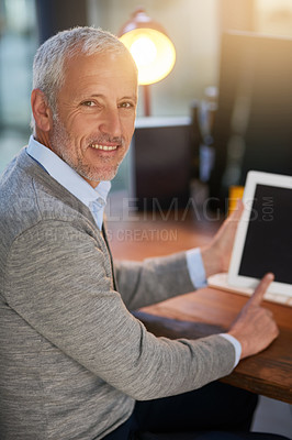 Buy stock photo Portrait of a mature businessman using his digital tablet in the office
