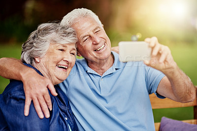 Buy stock photo Cropped portrait of an affectionate senior couple taking selfies in their backyard
