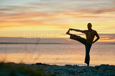 Buy stock photo Shot of a man practicing yoga at the beach during sunset