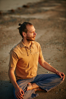 Buy stock photo Shot of a man sitting in the lotus position during his yoga routine at the beach