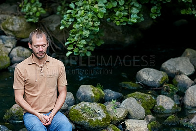 Buy stock photo Shot of a handsome man meditating outdoors