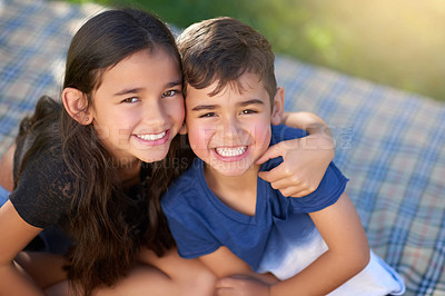 Buy stock photo Portrait of a pair of young siblings hugging each other while sitting in their backyard