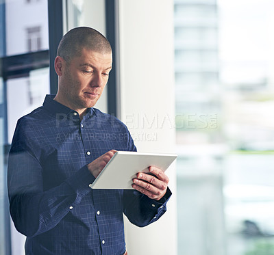 Buy stock photo Shot of a businessman using a digital tablet in a modern office