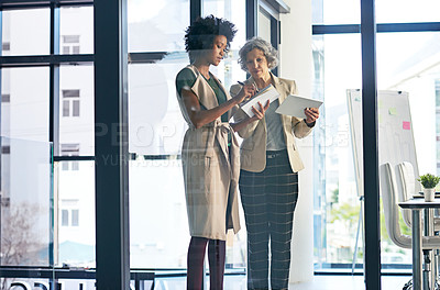 Buy stock photo Shot of two businesswomen making notes while discussing something on a tablet
