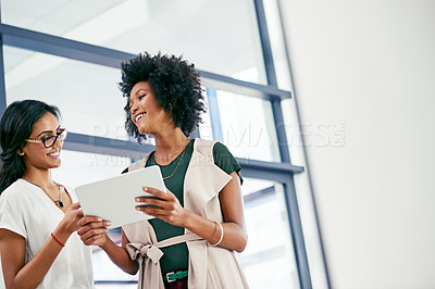 Buy stock photo Shot of two colleagues discussing something on a digital tablet
