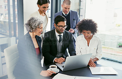 Buy stock photo Shot of a group of businesspeople coming together to discuss something on a laptop