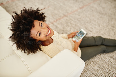 Buy stock photo Portrait of an attractive young using her cellphone while sitting on the floor at home