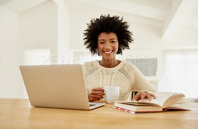 Buy stock photo Portrait of an attractive young using her laptop, reading a book and drinking some coffee at home