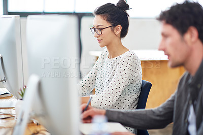 Buy stock photo Shot of two designers sitting at working on computers in an office