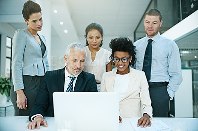 Buy stock photo Shot of a group of businesspeople coming together to work on something on a laptop