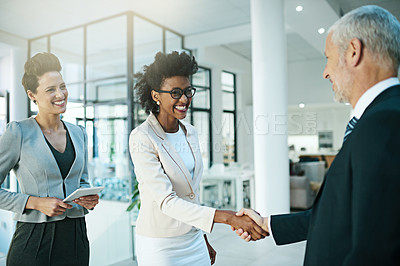 Buy stock photo Shot of businesspeople shaking hands in an modern office