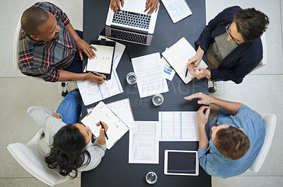 Buy stock photo High angle shot of a team of colleagues having a meeting in a office