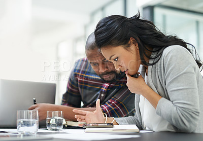 Buy stock photo Shot of two colleagues looking at a phone together during a meeting at work