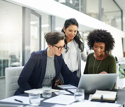 Buy stock photo Shot of a group of businesswomen using a laptop during a meeting at work