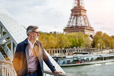 Buy stock photo Shot of a handsome mature man leaning on a railing in Paris with the Eiffel Tower in the background