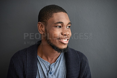 Buy stock photo Studio shot of a smiling young man standing against a gray background