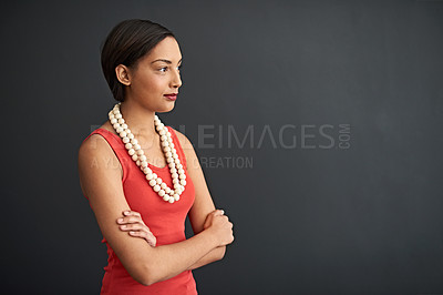 Buy stock photo Studio shot of a focused young woman standing with her arms crossed against a gray background